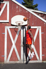 Black man dunking basketball outside barn