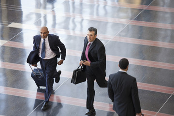 Hispanic businessmen running in airport