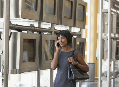 Black businesswoman talking on cell phone next to arrival departure board in airport