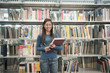 Smiling Chinese student holding book in library