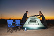 Couple in formal attire assembling tent in dessert at twilight