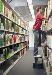 Hispanic student on footstool peering over library shelves
