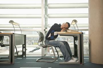 Hispanic student sleeping at library table