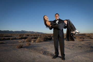 Man holding woman in formal attire in desert