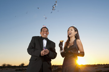 Couple in formal attire celebrating with champagne and confetti in desert at sunset