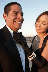 Woman adjusting bow tie on man