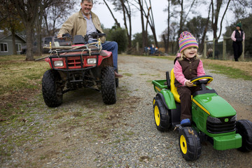 Caucasian grandfather and granddaughter on tractors