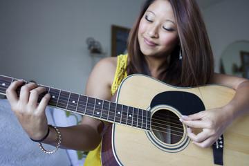 Mixed race teenage girl playing guitar