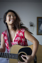 Smiling mixed race teenage girl playing guitar