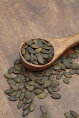 Close up of toasted pumpkin seeds in wooden spoon