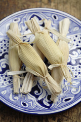 Wrapped corn tamales on plate