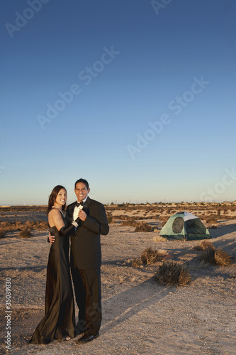 Smiling couple in formal attire standing outside tent in desert