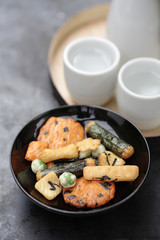 Close up of Japanese rice crackers and sake