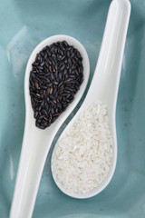 Black and white rice on spoons