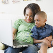 Black mother and son using laptop on sofa
