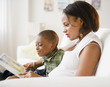 Black mother and son reading book on living room sofa