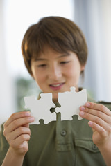 Mixed race boy connecting jigsaw pieces