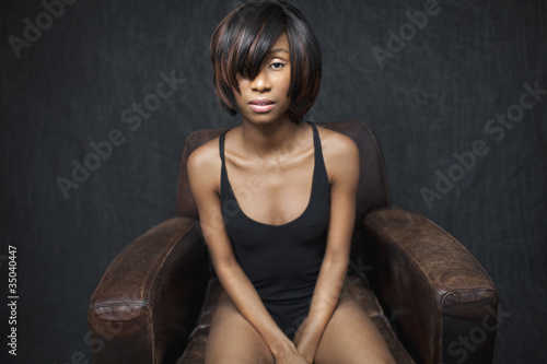 Black woman sitting in leather armchair