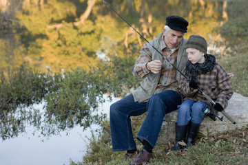 Caucasian grandfather fishing with grandson