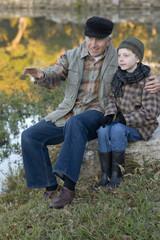 Caucasian grandfather sitting near lake with grandson
