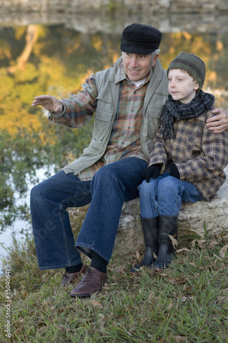 Caucasian grandfather sitting near lake with grandson