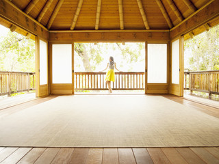 Asian woman standing on balcony of empty retreat