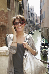 Smiling Italian woman talking on cell phone near canal