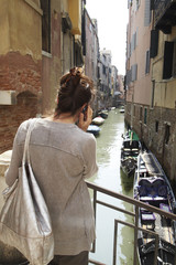 Italian woman talking on cell phone near canal