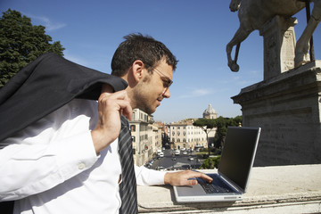 Italian businessman using laptop outdoors