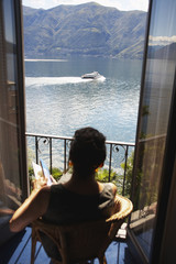 Italian woman sitting balcony looking at lake