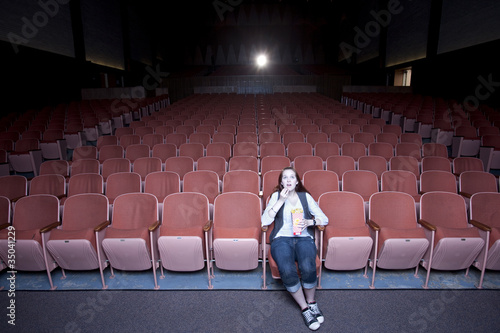 Caucasian woman watching move in empty theater