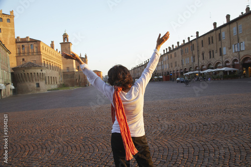 Italian woman with arms raised in piazza