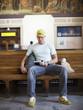 Caucasian man reading book in train station