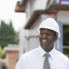 Smiling Black real estate agent in hard-hat near construction site