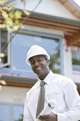 Black architect holding blueprints on construction site