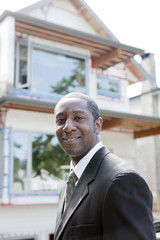Black real estate agent near house under construction