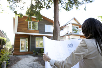 Mixed race real estate agent standing near house reviewing blueprints