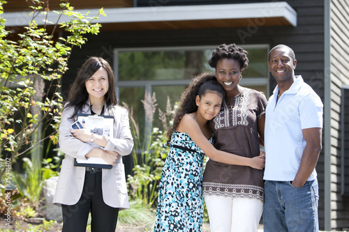 Real estate agent standing with family near house