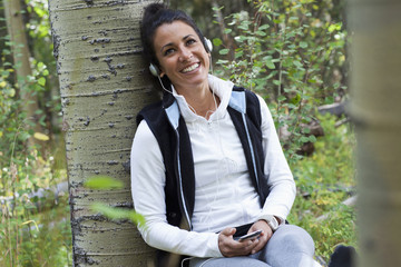 Hispanic woman leaning against tree listening to headphones