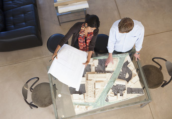 Architects reviewing building model in office