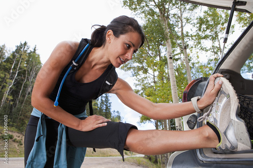 Hispanic woman stretching before exercise