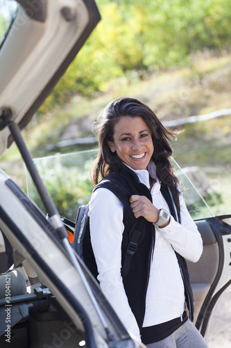 Hispanic woman with backpack getting out of car