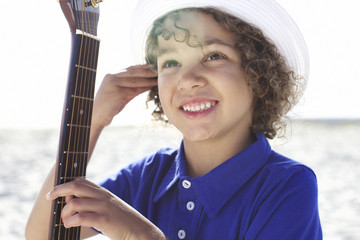 Mixed race boy holding guitar on beach