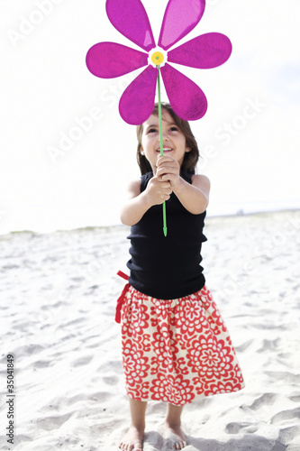 Hispanic girl playing with toy flower on beach