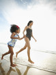 Hispanic mother and daughter holding hands and walking on beach