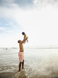 Black father lifting daughter while standing in ocean