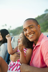Smiling father holding daughter on beach