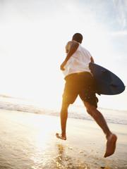 Black man running with surfboard on beach