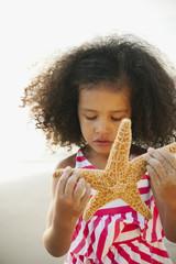 Mixed race girl holding starfish on beach