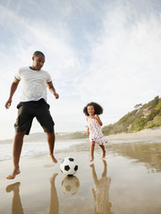 Black father kicking soccer ball with daughter on beach